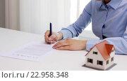 Купить «woman with house model and pen signing contract», видеоролик № 22958348, снято 14 мая 2016 г. (c) Syda Productions / Фотобанк Лори