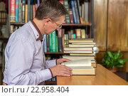 Купить «Мужчина в очках сидит за столом с книгами», фото № 22958404, снято 9 мая 2016 г. (c) Валерий Бочкарев / Фотобанк Лори