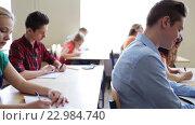 Купить «students with notebooks writing test at school», видеоролик № 22984740, снято 28 апреля 2016 г. (c) Syda Productions / Фотобанк Лори