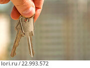 Купить «Ключи от квартиры в руке на фоне жилого  дома», фото № 22993572, снято 21 апреля 2016 г. (c) Сергеев Валерий / Фотобанк Лори