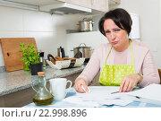 Купить «Upset woman with bills crying at home», фото № 22998896, снято 23 февраля 2019 г. (c) Яков Филимонов / Фотобанк Лори