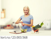 Купить «smiling woman cooking vegetable salad on kitchen», фото № 23003568, снято 26 апреля 2015 г. (c) Syda Productions / Фотобанк Лори