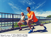 Купить «smiling couple stretching outdoors», фото № 23003628, снято 5 июля 2015 г. (c) Syda Productions / Фотобанк Лори