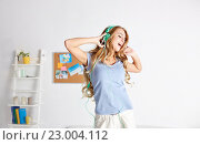 Купить «happy woman in headphones ihaving fun at home», фото № 23004112, снято 14 ноября 2015 г. (c) Syda Productions / Фотобанк Лори