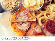 Купить «close up of fast food snacks and drink on table», фото № 23004224, снято 21 мая 2015 г. (c) Syda Productions / Фотобанк Лори