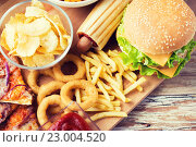 Купить «close up of fast food snacks on wooden table», фото № 23004520, снято 21 мая 2015 г. (c) Syda Productions / Фотобанк Лори