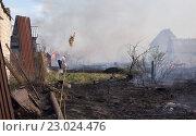 Купить «Окраина сада. Пожар. Обгорают саженцы, дома в дыму. Мужчина поливает из вёдер водой не сгоревший участок», фото № 23024476, снято 19 мая 2016 г. (c) Нина Карымова / Фотобанк Лори