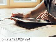 Женщина с планшетным компьютером в руках за столом возле окна. Стоковое фото, фотограф Константин Колосов / Фотобанк Лори