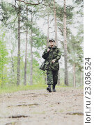 Купить «young soldier or hunter with gun in forest», фото № 23036524, снято 14 августа 2014 г. (c) Syda Productions / Фотобанк Лори