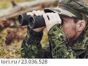 Купить «young soldier or hunter with binocular in forest», фото № 23036528, снято 14 августа 2014 г. (c) Syda Productions / Фотобанк Лори