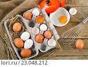 Купить «Raw eggs on a rustic wooden background.», фото № 23048212, снято 23 марта 2016 г. (c) Tatjana Baibakova / Фотобанк Лори