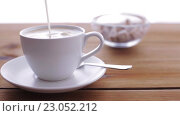 Купить «cream or milk pouring to coffee cup on table», видеоролик № 23052212, снято 15 апреля 2016 г. (c) Syda Productions / Фотобанк Лори