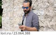 Купить «Man texting message on smartphone at stone wall», видеоролик № 23064388, снято 3 июня 2016 г. (c) Syda Productions / Фотобанк Лори