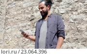 Купить «Man texting message on smartphone at stone wall», видеоролик № 23064396, снято 3 июня 2016 г. (c) Syda Productions / Фотобанк Лори