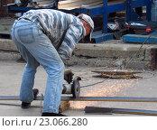 """Купить «Мужчина разрезает металлический уголок """"болгаркой""""», эксклюзивное фото № 23066280, снято 10 июня 2016 г. (c) Елена Осетрова / Фотобанк Лори"""