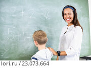 Купить «Smiling teacher assisting boy in doing addition on chalkboard», фото № 23073664, снято 6 марта 2016 г. (c) Wavebreak Media / Фотобанк Лори
