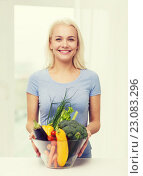 Купить «smiling young woman with vegetables at home», фото № 23083296, снято 26 апреля 2015 г. (c) Syda Productions / Фотобанк Лори
