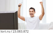 Купить «smiling man watching sports at home», фото № 23083872, снято 29 января 2015 г. (c) Syda Productions / Фотобанк Лори