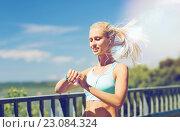 Купить «happy woman with heart rate watch and earphones», фото № 23084324, снято 5 июля 2015 г. (c) Syda Productions / Фотобанк Лори