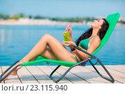 Девушка с коктейлем сидит в шезлонге на пляже. Стоковое фото, фотограф Кирилл Греков / Фотобанк Лори