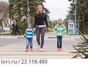 Купить «Анапа, Россия - 9 марта 2016: молодая мама с двумя дочками переходит дорогу по пешеходному переходу», фото № 23118480, снято 9 марта 2016 г. (c) Иванов Алексей / Фотобанк Лори