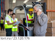 Купить «Focus on manager is talking on the phone and looking a clipboard», фото № 23120176, снято 23 марта 2016 г. (c) Wavebreak Media / Фотобанк Лори