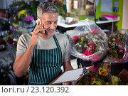 Купить «Male florist taking order on mobile phone», фото № 23120392, снято 17 апреля 2016 г. (c) Wavebreak Media / Фотобанк Лори