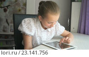 Купить «Девочка с планшетом сидит за столом», видеоролик № 23141756, снято 21 июня 2016 г. (c) worker / Фотобанк Лори
