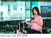 Купить «Женщина в зале ожидания смотрит на смартфон», фото № 23157056, снято 14 июня 2016 г. (c) Дмитрий Травников / Фотобанк Лори