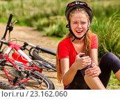 Girl fell off bike. Cyclist keeps self for bruised knee. Стоковое фото, фотограф Gennadiy Poznyakov / Фотобанк Лори