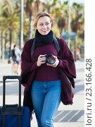 Купить «Young woman looking and taking pictures outdoors», фото № 23166428, снято 25 июня 2018 г. (c) Яков Филимонов / Фотобанк Лори