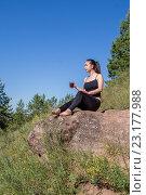 Девушка сидит на камне и держит кружку с напитком. Стоковое фото, фотограф Виктор Хван / Фотобанк Лори