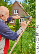 Купить «Седой мужчина точит косу перед своим загородным домом», фото № 23181476, снято 22 июня 2016 г. (c) Георгий Дзюра / Фотобанк Лори