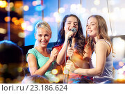 Купить «three happy women singing on night club stage», фото № 23186624, снято 20 октября 2014 г. (c) Syda Productions / Фотобанк Лори
