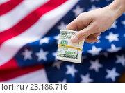 Купить «close up of hand with money over american flag», фото № 23186716, снято 6 мая 2016 г. (c) Syda Productions / Фотобанк Лори