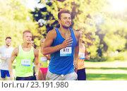 Купить «happy young sportsmen racing wit badge numbers», фото № 23191980, снято 16 августа 2015 г. (c) Syda Productions / Фотобанк Лори