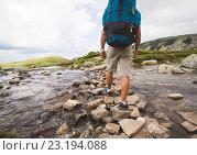 Мужчина с рюкзаком за спиной идет по камням в горной реке. Стоковое фото, фотограф Кирилл Греков / Фотобанк Лори