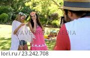 Купить «Two girls posing for his friends taking pictures», видеоролик № 23242708, снято 14 декабря 2018 г. (c) Wavebreak Media / Фотобанк Лори