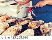 Купить «close up of cook hands grilling fish on street», фото № 23258696, снято 7 февраля 2015 г. (c) Syda Productions / Фотобанк Лори
