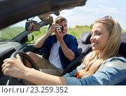 Купить «man photographing woman driving car by film camera», фото № 23259352, снято 28 мая 2016 г. (c) Syda Productions / Фотобанк Лори