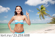 happy woman in bikini swimsuit pointing finger up. Стоковое фото, фотограф Syda Productions / Фотобанк Лори