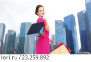Купить «happy woman with shopping bags over singapore city», фото № 23259892, снято 1 июня 2014 г. (c) Syda Productions / Фотобанк Лори