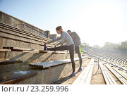 Купить «couple stretching leg on stands of stadium», фото № 23259996, снято 17 октября 2015 г. (c) Syda Productions / Фотобанк Лори