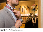 Купить «close up of man tying tie at clothing store mirror», фото № 23260040, снято 1 апреля 2016 г. (c) Syda Productions / Фотобанк Лори