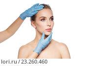 Купить «surgeon or beautician hands touching woman face», фото № 23260460, снято 14 апреля 2016 г. (c) Syda Productions / Фотобанк Лори