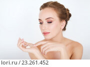 Купить «happy young woman with moisturizing cream on hand», фото № 23261452, снято 14 апреля 2016 г. (c) Syda Productions / Фотобанк Лори