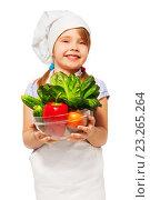 Купить «Улыбающаяся девочка в поварском колпаке со свежими овощами в руках на белом фоне», фото № 23265264, снято 9 апреля 2016 г. (c) Сергей Новиков / Фотобанк Лори
