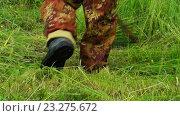 Купить «Движущаяся камера снимает крупным планом ноги мужчины,косящего траву косой», видеоролик № 23275672, снято 17 июля 2016 г. (c) Георгий Дзюра / Фотобанк Лори