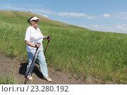 Купить «Пожилая женщина занимается скандинавской ходьбой с палками летом на природе», фото № 23280192, снято 13 июня 2016 г. (c) Наталия Макарова / Фотобанк Лори