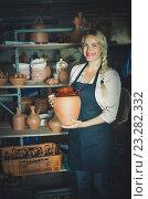 Купить «Portrait of glad woman pottery worker with ceramic crockery», фото № 23282332, снято 17 июля 2019 г. (c) Яков Филимонов / Фотобанк Лори